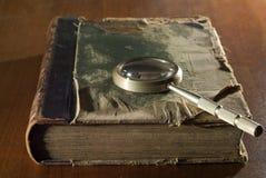 Un libro antico in una copertura stracciata ed in una lente d'ingrandimento Fotografia Stock