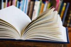 Un libro aperto in biblioteca Immagini Stock