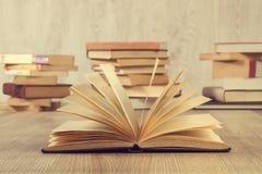 Un libro aperto e pile di libri Fotografie Stock