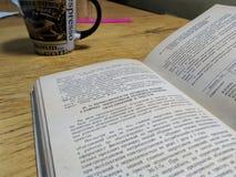 un libro aperto e una tazza sulla tavola Fotografie Stock Libere da Diritti
