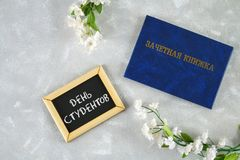 Un libro blu con un'iscrizione nel Russo - un registro del ` s dello studente Fiori bianchi su una priorità bassa grigia Iscrizio Immagine Stock