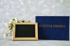 Un libro blu con un'iscrizione nel Russo - un registro del ` s dello studente Fiori bianchi su una priorità bassa grigia Giorno d Fotografia Stock Libera da Diritti