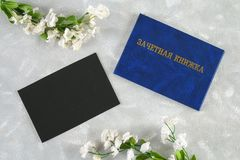 Un libro blu con un'iscrizione nel Russo - un registro del ` s dello studente Fiori bianchi su una priorità bassa grigia Giorno d Fotografia Stock