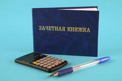 Un libro blu con un'iscrizione nel Russo - un registro del ` s dello studente Penna, calcolatore su un fondo blu Giorno degli stu Immagini Stock