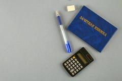 Un libro blu con un'iscrizione nel Russo - un registro del ` s dello studente Penna, calcolatore su un fondo grigio Giorno del `  Fotografia Stock Libera da Diritti
