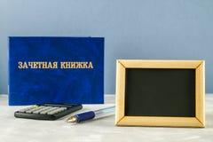 Un libro blu con un'iscrizione nel Russo - un registro del ` s dello studente Penna, calcolatore su un fondo grigio Giorno del `  Immagini Stock Libere da Diritti
