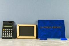 Un libro blu con un'iscrizione nel Russo - un registro del ` s dello studente Penna, calcolatore su un fondo grigio Giorno del `  Immagine Stock Libera da Diritti