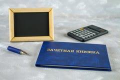 Un libro blu con un'iscrizione nel Russo - un registro del ` s dello studente Penna, calcolatore su un fondo grigio Giorno del `  Immagini Stock