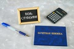 Un libro blu con un'iscrizione nel Russo - un registro del ` s dello studente Penna, calcolatore su un fondo grigio Iscrizione in Fotografie Stock