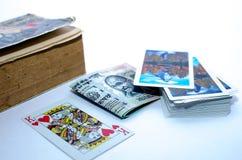 Un libro, carte da gioco, valuta o soldi tenuti insieme Immagini Stock