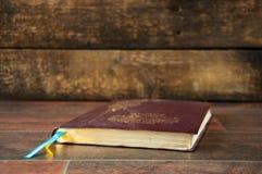 Un libro cerrado en una tabla de madera Biblia en fondo de madera fotos de archivo
