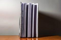 Un libro, un cuaderno con un modelo a cuadros en una tabla de madera en diversas actitudes La cubierta es gris y suave con textur fotografía de archivo