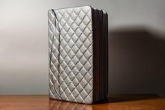 Un libro, un cuaderno con un modelo a cuadros en una tabla de madera en diversas actitudes La cubierta es gris y suave con textur imagen de archivo libre de regalías
