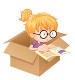 Un libro de lectura de la muchacha en una caja Fotografía de archivo