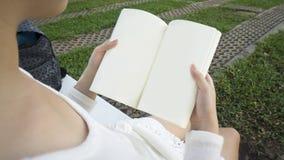 Un libro femminile della tenuta delle mani fotografia stock