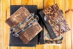 Un libro viejo limitado por una cadena brillante del metal La literatura prohibida arregló en una tabla de madera foto de archivo libre de regalías
