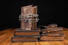 Un libro viejo limitado por una cadena brillante del metal La literatura prohibida arregló en una tabla de madera fotografía de archivo libre de regalías
