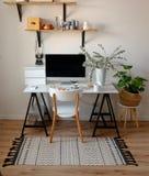 Un lieu de travail chic dans le style scandinave Chaise blanche, sur la table d'ordinateur et l'eucalyptus dans un pot blanc Photo libre de droits