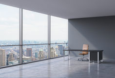 Un lieu de travail dans un bureau panoramique faisant le coin moderne à New York, Manhattan Une chaise en cuir brune et une table Image stock