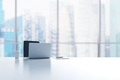 Un lieu de travail dans un bureau panoramique moderne à Singapour Un ordinateur portable, le bloc-notes et une tasse de café sont Photos stock