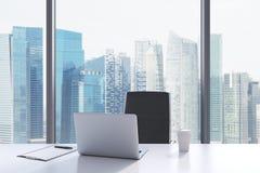 Un lieu de travail dans un bureau panoramique moderne avec la vue de Singapour Image stock