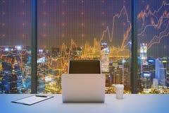 Un lieu de travail dans un bureau panoramique moderne avec la vue de soirée de New York et le diagramme financier au-dessus de la Image libre de droits