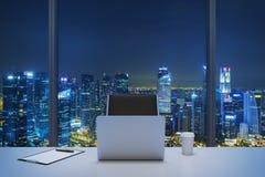 Un lieu de travail dans un bureau panoramique moderne avec la vue de soirée de New York Une table blanche, chaise en cuir noire Image libre de droits