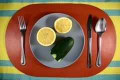 Un limón y un pepino cortados en una placa Fotos de archivo libres de regalías