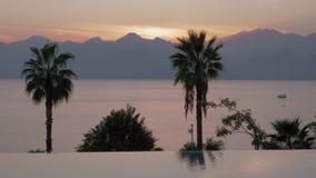 Un limite aperto della piscina e una vista uguagliante del mare contro le montagne archivi video