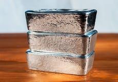 Un lingotto d'argento di tre colate su un fondo di mogano fotografie stock