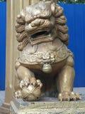 Un lion en pierre est situé à côté de la porte en pierre dans le parc d'Euko images stock