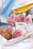Un lit blanc, paquets avec des cadeaux, café frais, gâteaux de petit déjeuner et un bouquet des roses roses Photo de vintage bonj photos stock
