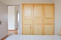 Un lit en bois et une garde-robe dans la chambre à coucher moderne photo libre de droits