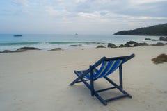 Un lit pliant solitaire et vide sur la plage photographie stock libre de droits