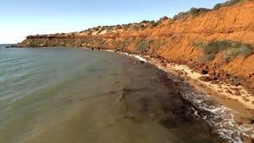 Un litorale ed il mare con i cieli e le scogliere stock footage