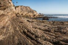 Un littoral Pacifique avec les falaises jaunes et les vagues de grès précipitant la plage photos stock