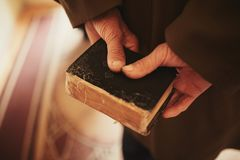 Un livre dans les mains d'un vieil homme petite bible images libres de droits