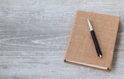 Un livre de journal intime et un stylo sur le fond en bois Photo stock
