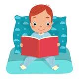 Un livre de lecture de garçon sur le lit Photo stock