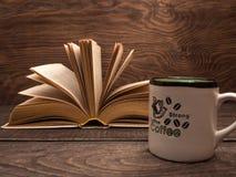 Un livre et une tasse de café fort sur une table en bois Photographie stock libre de droits
