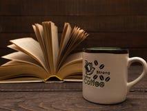 Un livre et une tasse de café fort sur une table en bois Image stock
