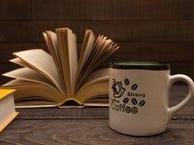 Un livre et une tasse de café fort sur une table en bois Image libre de droits