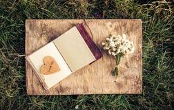 Un livre ouvert avec les pages vides, un bouquet des fleurs blanches et un coeur en bois Concept romantique Copiez l'espace Images stock
