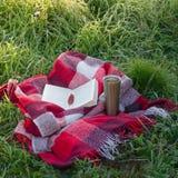 Un livre ouvert dans le jardin, livre, un thermos avec le thé, une vapeur au-dessus d'une tasse thermo Couverture chaude Ouvrez l images libres de droits