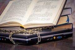 Un livre ouvert se trouve sur un ordinateur portable qui est lié par une chaîne Livres au lieu des ordinateurs Amour au read_ photo libre de droits