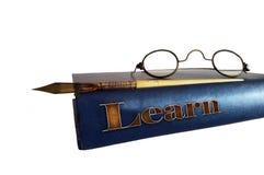 Un livre plus ancien avec une paire des verres de mamie et d'un vieux stylo-plume sur un fond blanc Images stock
