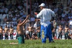 Un lottatore supplica con un arbitro al festival lottante dell'olio turco di Elmali in Turchia immagini stock