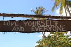 """Un """"Love usted mismo de la inscripción y  del everyone†en la choza abandonada de madera Fotografía de archivo libre de regalías"""