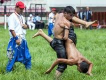 Un luchador joven cría a su opositor hacia el cielo durante la competencia en el festival de lucha del aceite turco de Kirkpinar  Fotografía de archivo