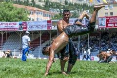 Un luchador levanta a su opositor hacia el cielo durante la competencia en el festival de lucha del aceite turco de Elmali en Elm Imagenes de archivo